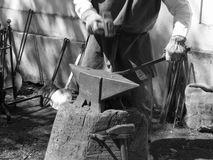 Blacksmith manually forging the molten metal with hammer on the anvil . Black and white photo Stock Photos