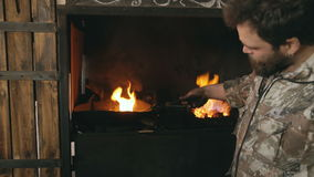 Blacksmith manually temper steel knife in cold oil near fireplace in traditional smithy stock video footage