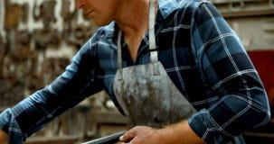 Blacksmith measuring metal rod with caliper 4k. Blacksmith measuring metal rod with caliper in workshop 4k stock video