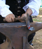 Blacksmith - motion blur on hammer. Blacksmith at a renaissance faire Stock Photo