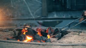 A blacksmith moves coal while they heat. 4K stock video footage