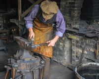 Blacksmith in period costume Working at Old World Wisconsin royalty free stock photo