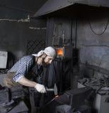 Blacksmith pracujący metal z młotem na kowadle w kuźni zdjęcie stock