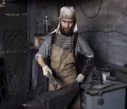 Blacksmith pracujący metal z młotem na kowadle w kuźni fotografia stock