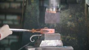 Blacksmith pracuje z elektrycznym młotem na kowadle, mężczyzna robi dobrze kształtowi gorąca stal, rzemiosło zdjęcie wideo