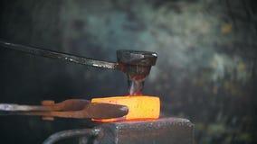 Blacksmith pracuje z elektrycznym młotem na kowadle, mężczyzna robi dziury w gorącej stali, rzemiosło zdjęcie wideo