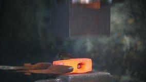 Blacksmith pracuje z elektrycznym młotem na kowadle, pracownik robi dziury w gorącej stali, rzemiosło zbiory