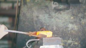 Blacksmith pracuje z elektrycznym młotem na kowadle, robi dobrze kształtowi gorąca stal, rzemiosło zbiory