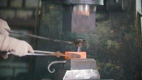 Blacksmith pracuje z elektrycznym młotem na kowadle, robi dziury w gorącej stali, rzemiosło zbiory