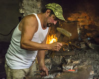Blacksmith preparing a horseshoe. Blacksmith shaping a horseshoe by hitting it with the hammer while it is red-hot Royalty Free Stock Photo