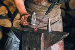 Blacksmith is processing a hot metal object of a spiral shape at anvil in a workshop stock photo