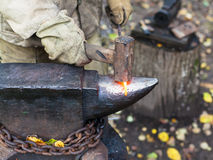 Blacksmith processing red hot iron rod on anvil Stock Photography