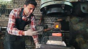 Blacksmith przy pracą z elektrycznym młotem blisko kowadła, gorąca stal, rzemiosło portret zdjęcie wideo