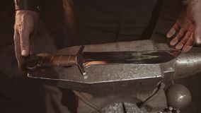 The blacksmith puts the finished forged knife on the anvil. The end of serious work. Beautiful product is ready.