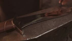 The blacksmith puts the finished forged knife on the anvil. Super close-up