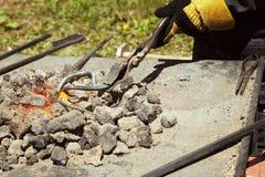 Blacksmith ręka trzyma metalu zawijas w tongs na gorący jarzyć się bunkruje Obraz Stock