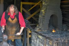 Blacksmith with Red Shirt in Blacksmith Shop Stock Images