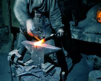 Blacksmith`s hands with smith`s hammer are hot metal heated. The blacksmith`s hands with the smith`s hammer are hot metal heated. The concept of manual labor and royalty free stock photos