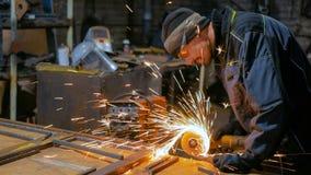 Blacksmith sawing metal with hand circular saw. Professional blacksmith sawing metal with hand circular saw at forge, workshop. Handmade, craftsmanship and royalty free stock image