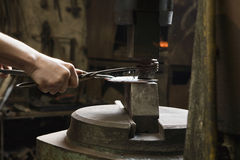Blacksmith Shaping Metal In Workshop Stock Image