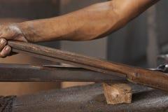 Blacksmith sharpening a blade royalty free stock photos