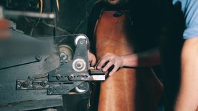 Blacksmith sharpens metal knife on a rotating machine at a forge. 4K stock footage