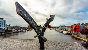 Blacksmith structure with padlocks that sits on a bridge. With the river Shannon and the village of Athlone in the background, wonderful sunny day in the county royalty free stock image
