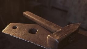 Blacksmith takes an anvil with a huge hammer for forging metal products. Cinematic plan.