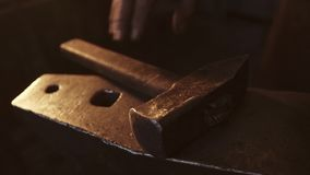 Blacksmith takes an anvil with a huge hammer for forging metal products. Close up