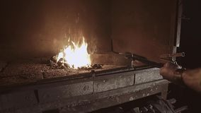 Blacksmith takes a red-hot workpiece in the oven and turns it over for uniform heating. Close-up process.