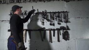 Blacksmith Taking Tongs and Hammer for Forging