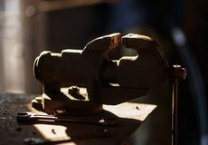 Blacksmith tools. Backlighted old vise in a forge shop Stock Photo