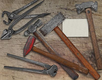 Blacksmith tools and business card over bench Royalty Free Stock Photos