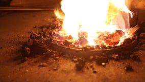 Blacksmith używa starą łopatę podsycać w górę płomieni wśrodku węglowej kuźni dla pracującego metalu zbiory wideo