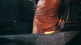 Blacksmith is using hammer to forge metal. HD stock footage