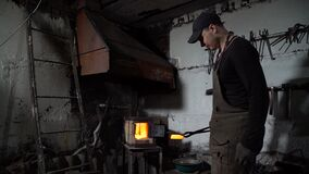 Blacksmith Using Tongs for Holding Red Hot Metal