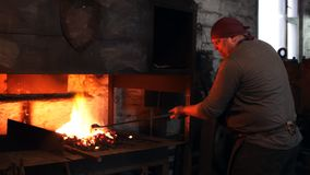 Blacksmith warms the stove. Sparks fly out from under the blacksmith`s hammer stock footage