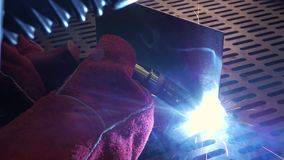 A blacksmith or welde. A blacksmith or welder, with his welder, welding steel and iron, in extreme slow motion. The welder uses a mask to protect your eyes from stock video