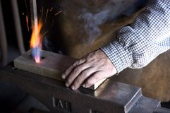 Blacksmith at Work. Blacksmith demonstrating how to drill holes in wood royalty free stock photography