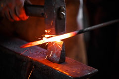 Blacksmith at work. The hands of a blacksmith at work in the smithy royalty free stock image