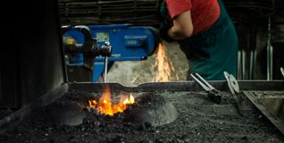 Blacksmith at work. Hit with a hammer by a hot metal on the anvil Stock Photo