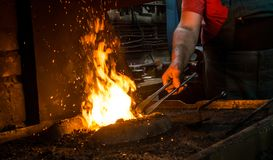 Blacksmith at work. Hit with a hammer by a hot metal on the anvil Royalty Free Stock Photos