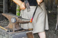 Blacksmith in a work kilt pounding a red hot piece of metal with a hammer on an anvil - hands in motion stock photography