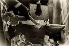 Blacksmith at work. Young man in the smithy works with forged metal Stock Image