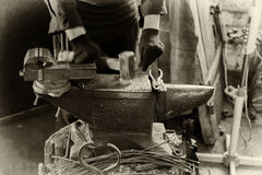 Blacksmith at work. Young man in the smithy works with forged metal Royalty Free Stock Image