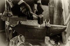 Blacksmith at work. Young man in the smithy works with forged metal Stock Photography