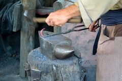 Blacksmith Working on Anvil. In period costume at mission Stock Photo