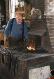 A blacksmith working black metal in a historical 100 year old (smithy) blacksmith shop in Galena Stock Image