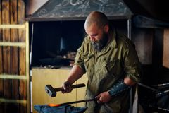 Blacksmith working in the forge. Manufacture of parts and weapons from molten metal, using the hammer and anvil. Blacksmith working in the forge. Manufacture of Royalty Free Stock Photography