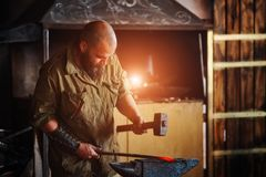 Blacksmith working in the forge. Manufacture of parts and weapons from molten metal, using the hammer and anvil. Blacksmith working in the forge. Manufacture of Royalty Free Stock Photos